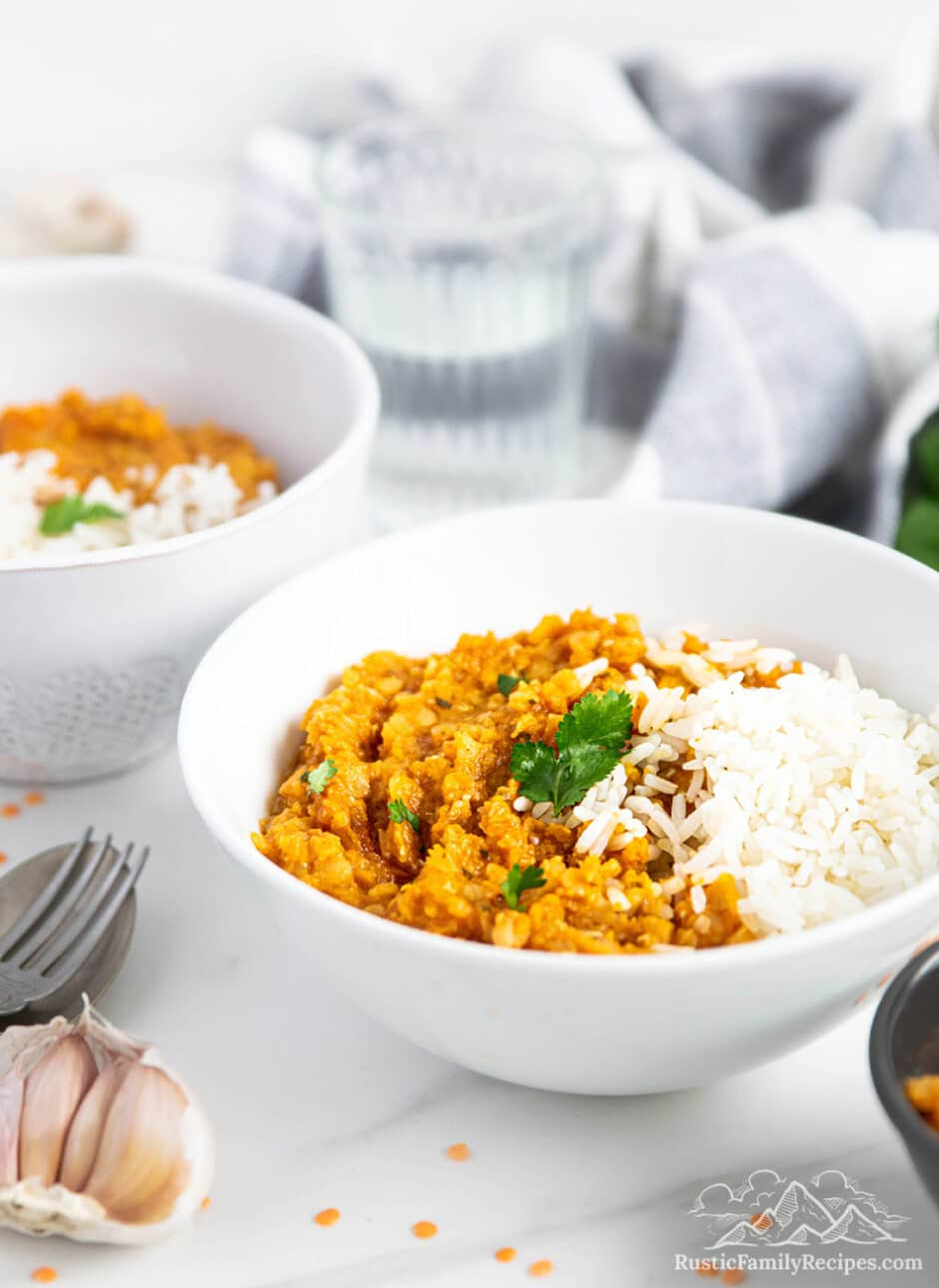 Two white bowls with sweet potato dhal
