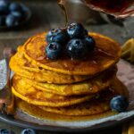 A stack of pumpkin pancakes topped with blueberries with syrup being poured