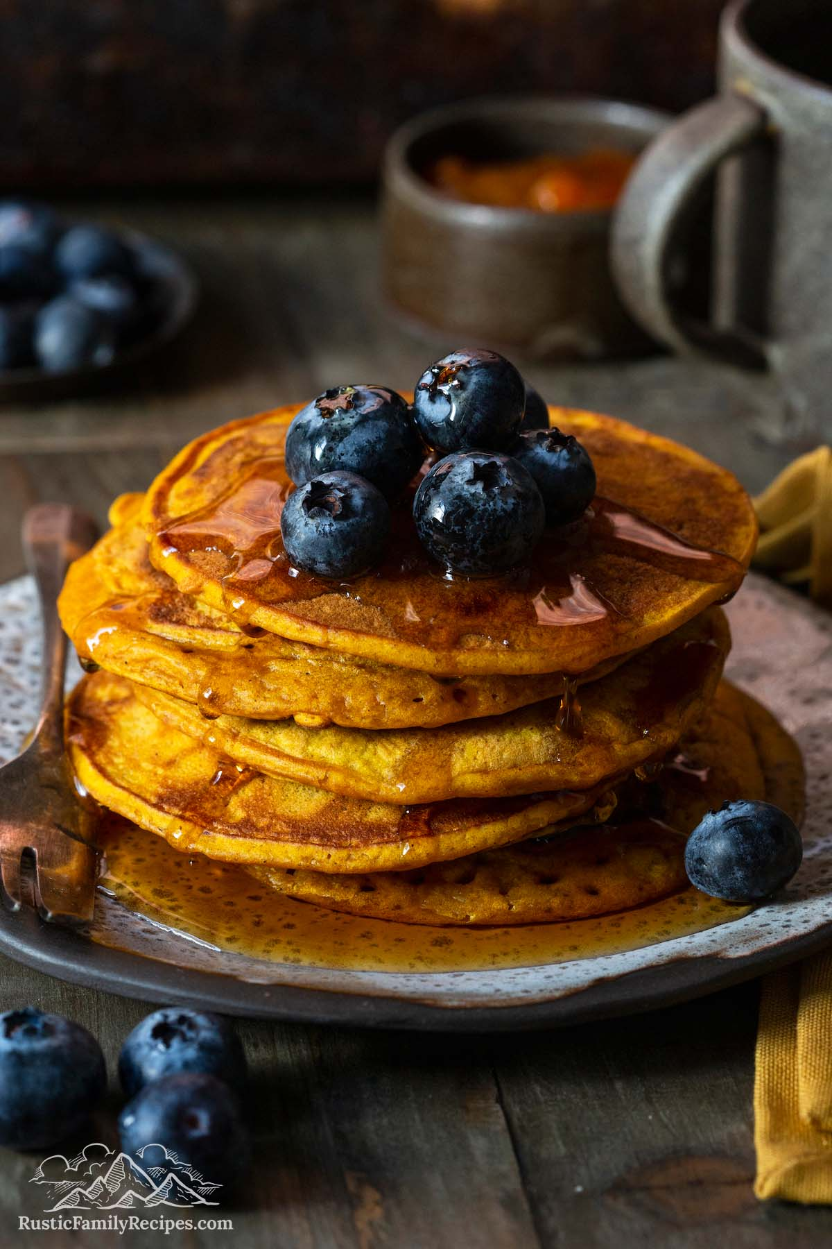 Tall stack of pumpkin pancakes with blueberries and syrup