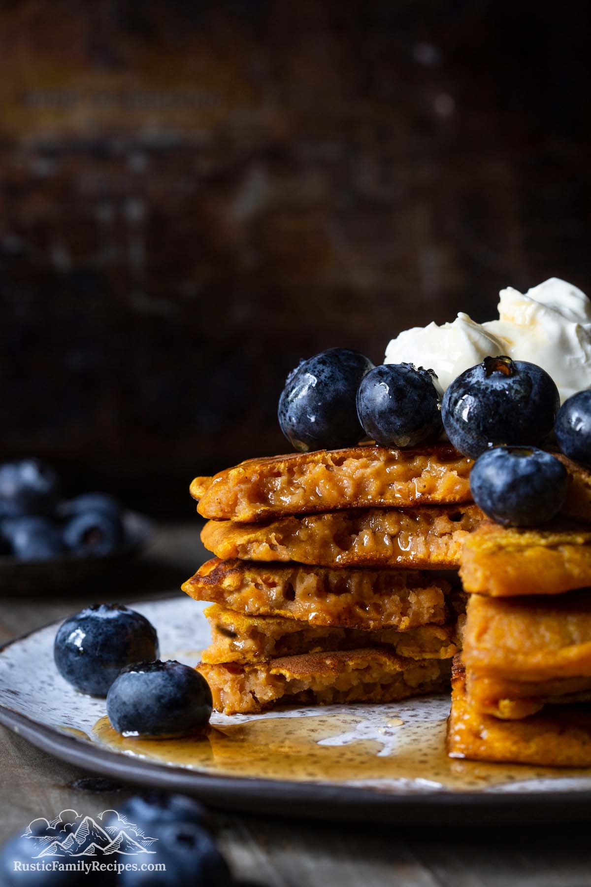 Stack of pumpkin pancakes with blueberries and whipped cream, with a slice taken out
