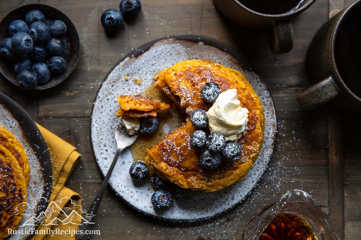 A stack of pancakes with blueberries, whipped cream and powdered sugar, top view