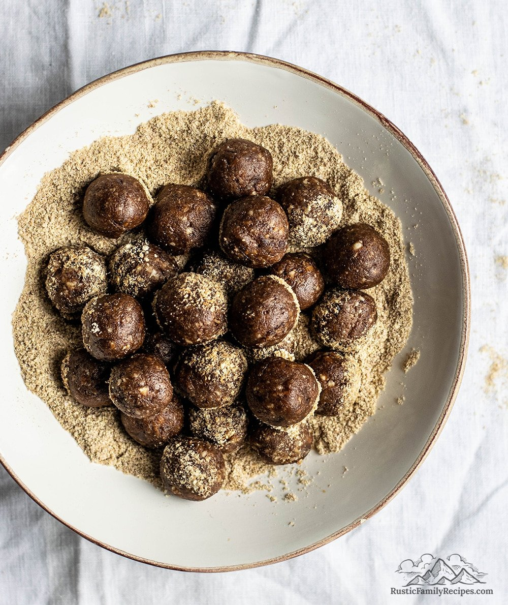 A white bowl filled with chocolate almond energy bites.