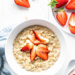 A bowl of steel cut oatmeal topped with strawberries