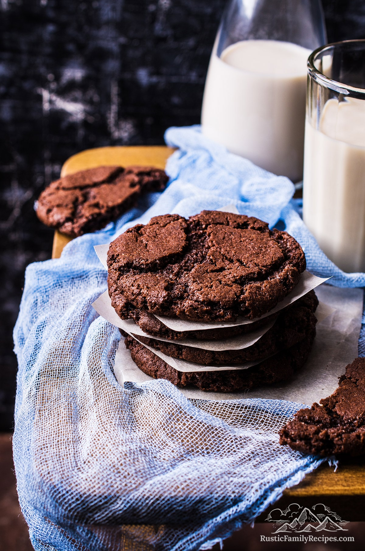 A stack of chocolate cookies next to glasses of milk