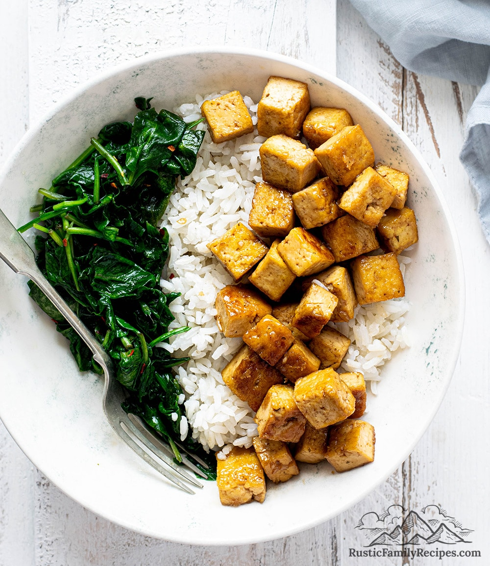 A bowl of maple tofu with sticky rice and spinach
