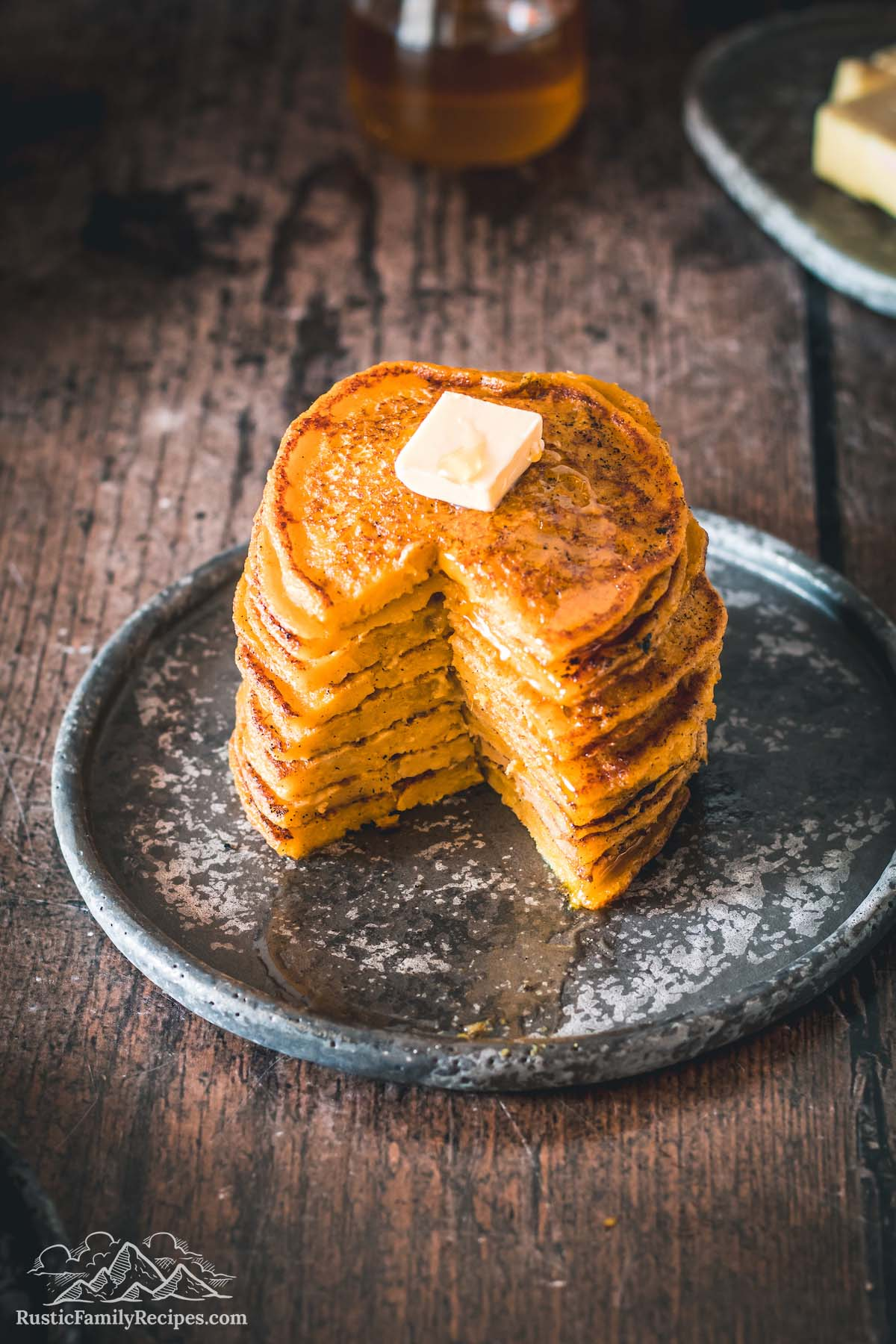 Stack of pumpkin corn cakes with a slice taken out so you can see the inside.