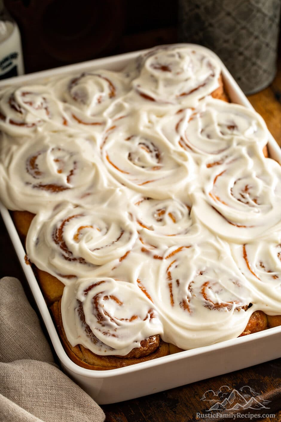 A white baking dish with frosted cinnamon rolls freshly baked.