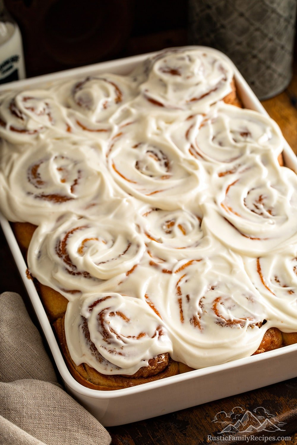A white baking dish filled with frosted cinnamon buns.