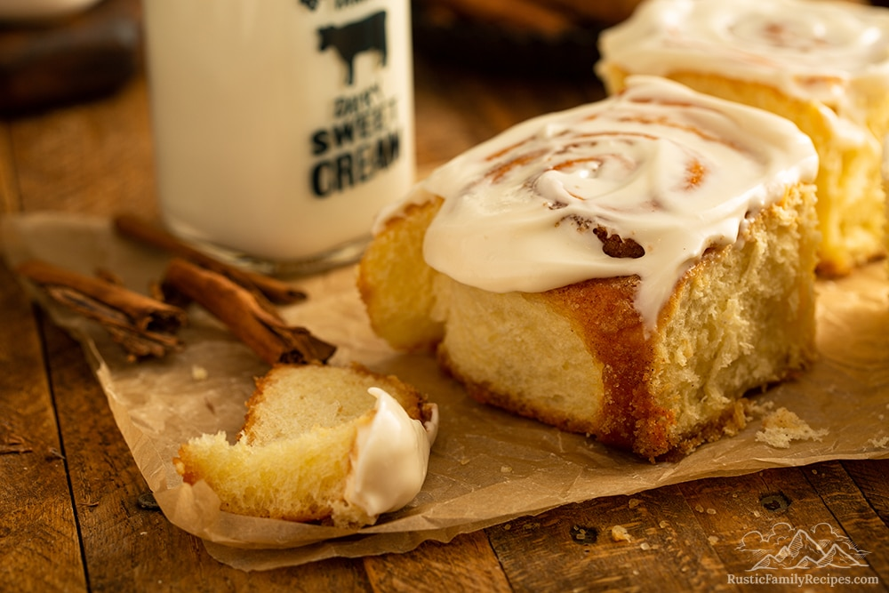 A single frosted cinnamon bun on parchment paper with milk.