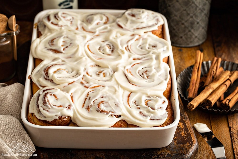 A white dish with homemade cinnamon buns frosted, next to cinnamon sticks.