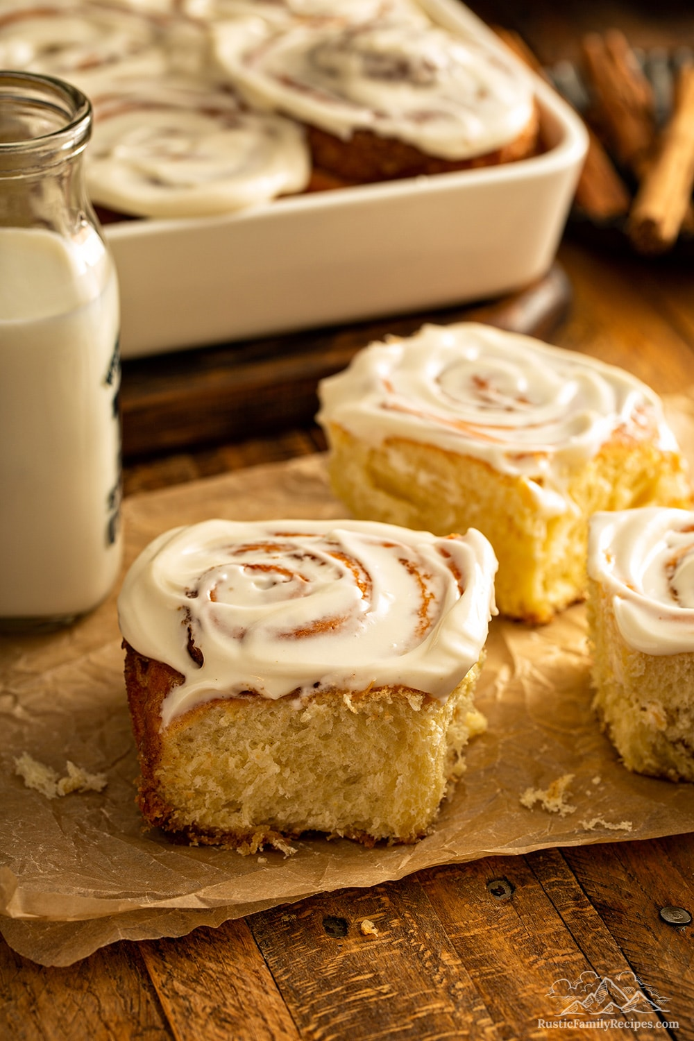 Three cinnamon rolls in front of a baking dish and a jar of milk