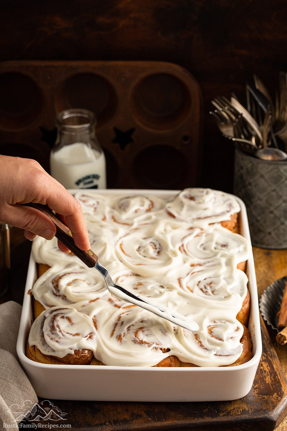 Cinnamon rolls being frosted in a white baking dish on a wooden table.