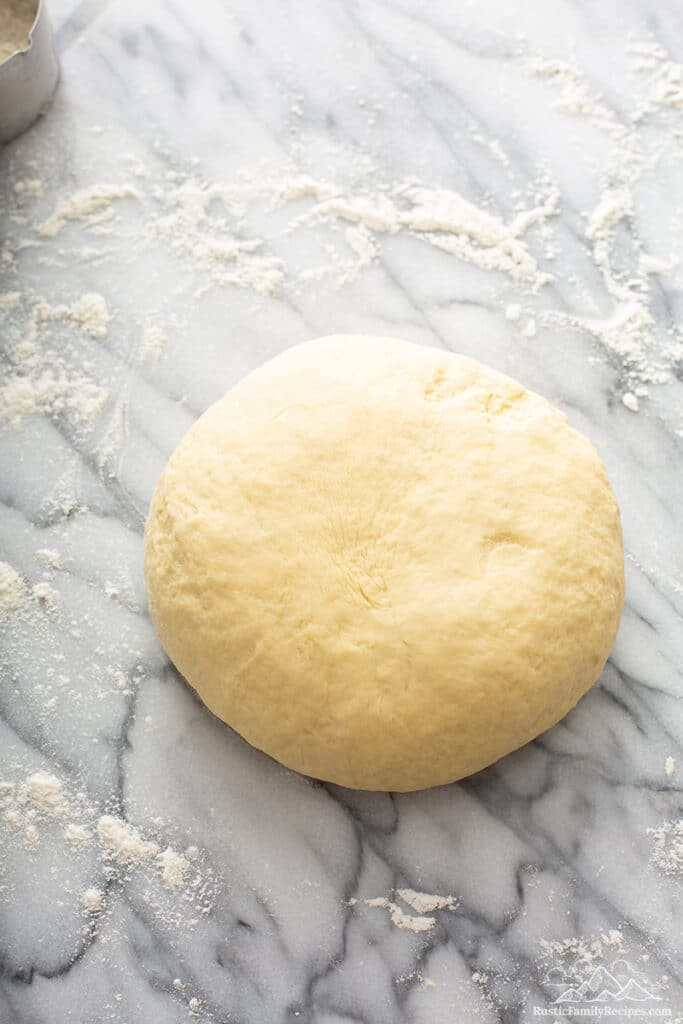 A ball of dough on a marble counter.