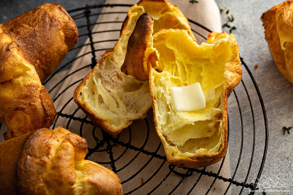 A pile of popovers, one sliced with melted butter inside.