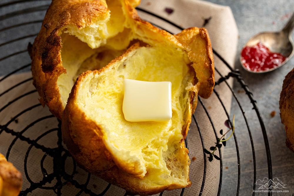 Sliced open popover with melting butter, next to a spoonful of jam.