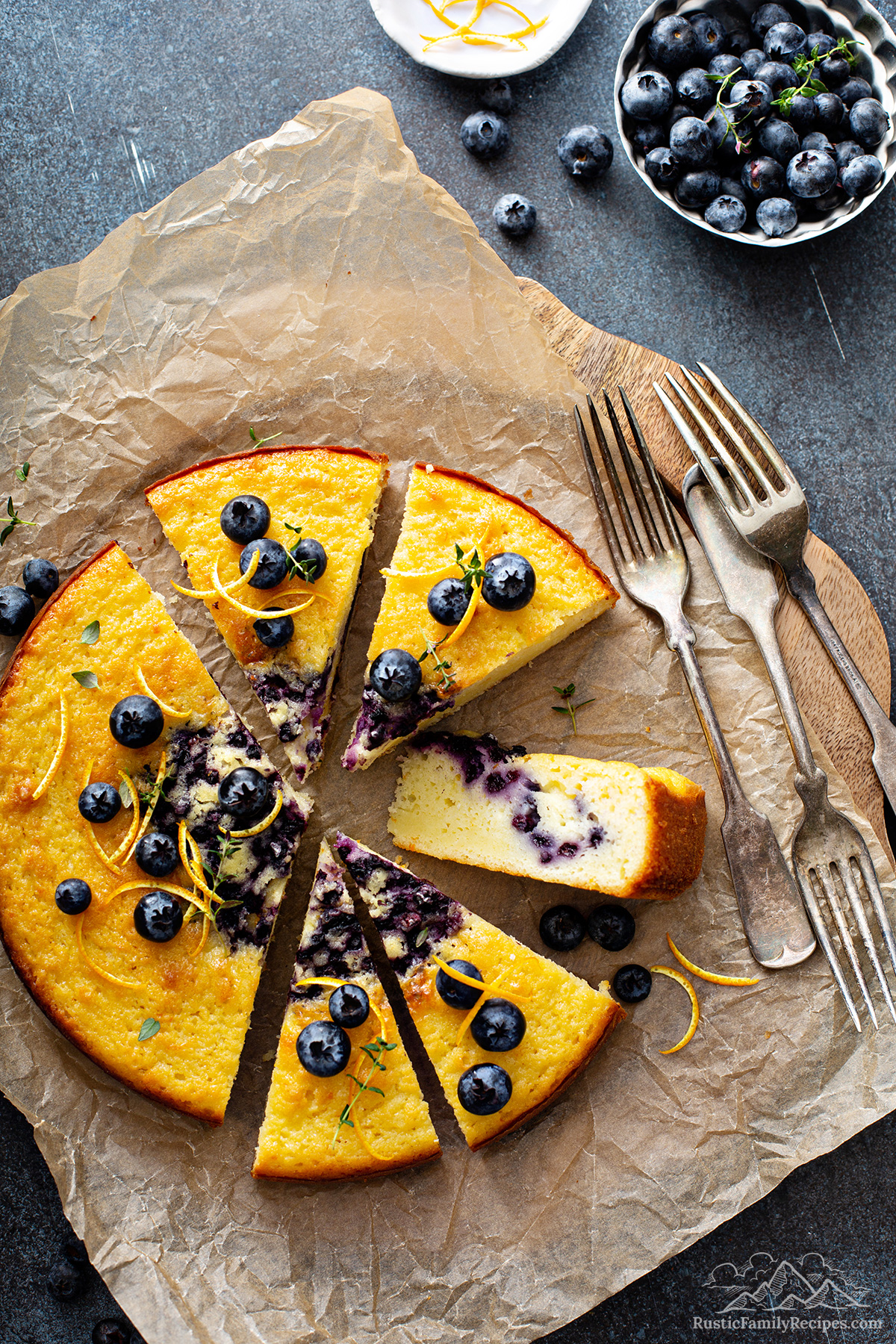 A sliced blueberry coffee cake on parchment next to rustic forks.