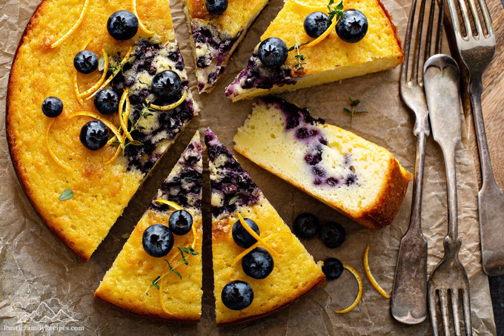 Sliced blueberry coffee cake on parchment paper next to forks.