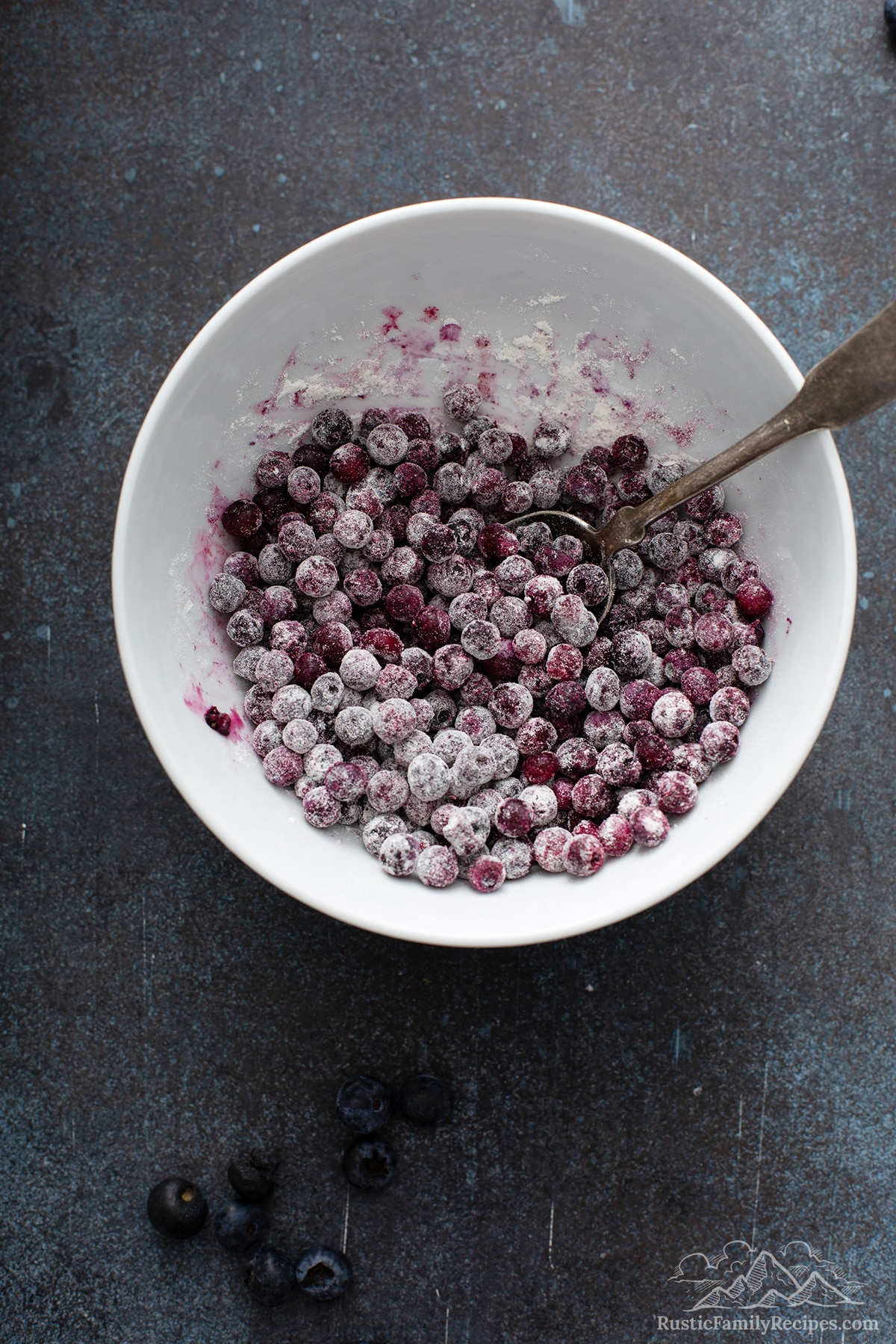 A white bowl with frozen blueberries tossed with flour mixture