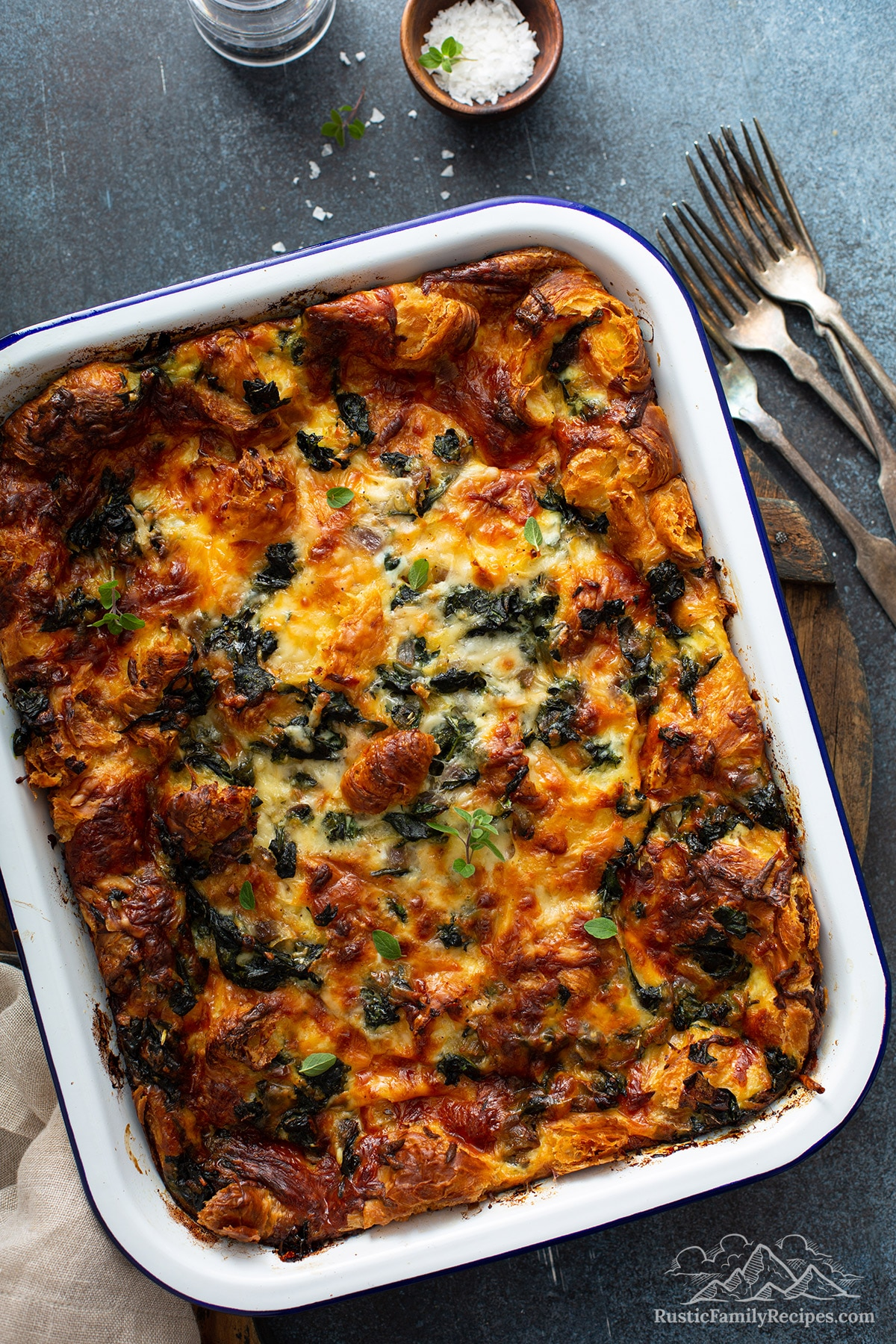 A cooked croissant strata in a white baking dish.