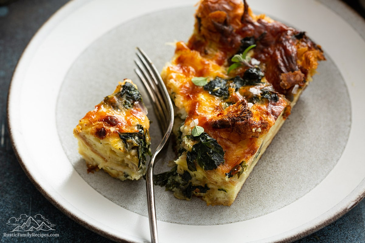 A slice of spinach strata on a while plate with a fork