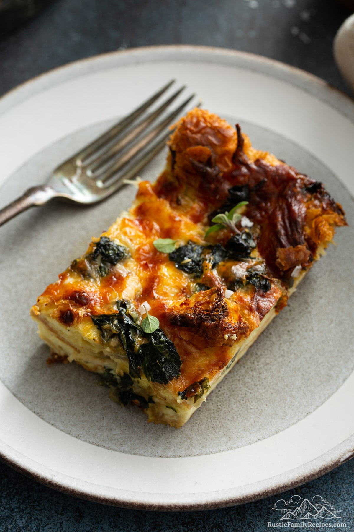A slice of spinach strata on a plate with a fork