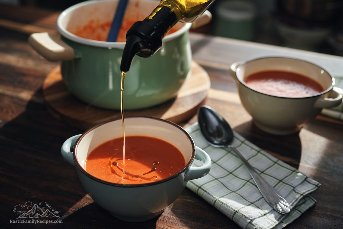 Olive oil poured into tomato soup.