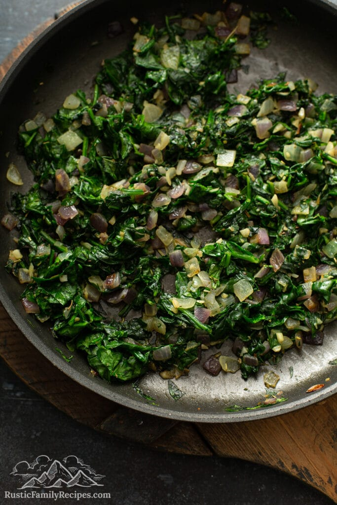 Onions and spinach cooking in a pan