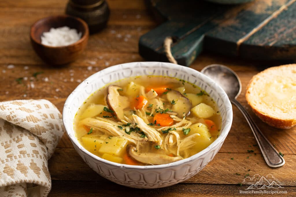 A bowl of ip chicken soup on a wood table next to a spoon and slice of bread.