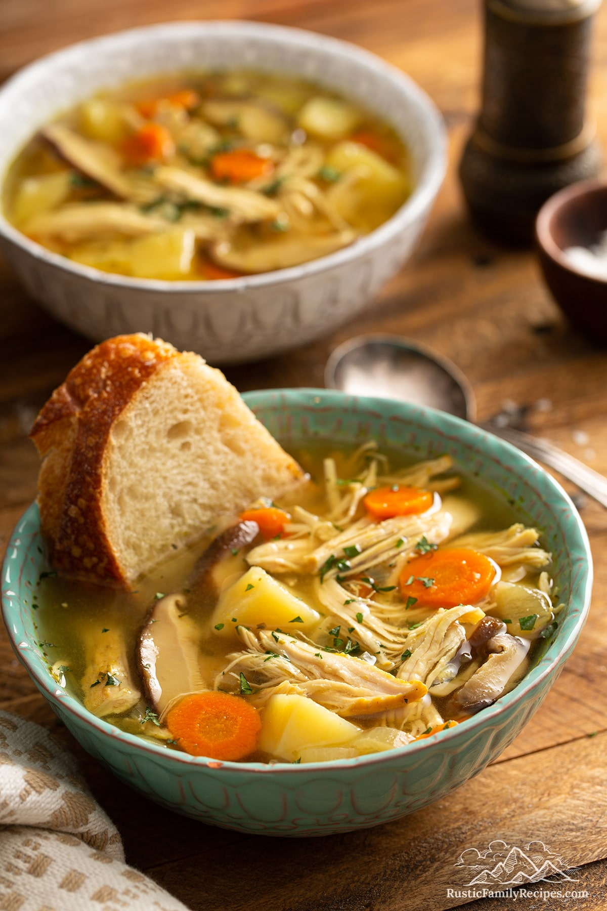 A bowl of IP chicken soup with a crust of bread in the soup.