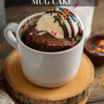 A chocolate cake in a mug topped with ice cream and sprinkles, a spoon with some cake scooped out