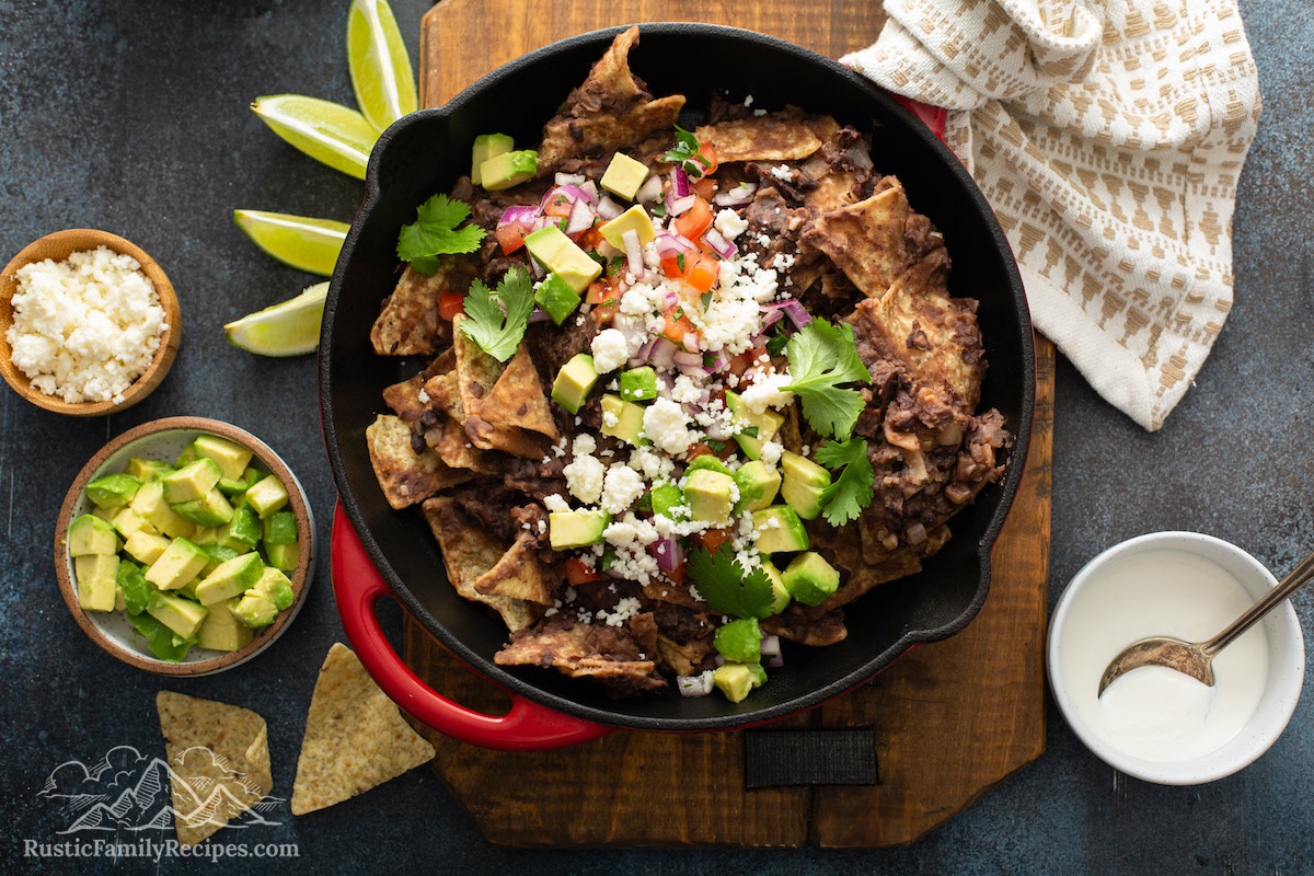 Black bean chilaquiles in a red pan with avocado, cheese, sour cream and limes.