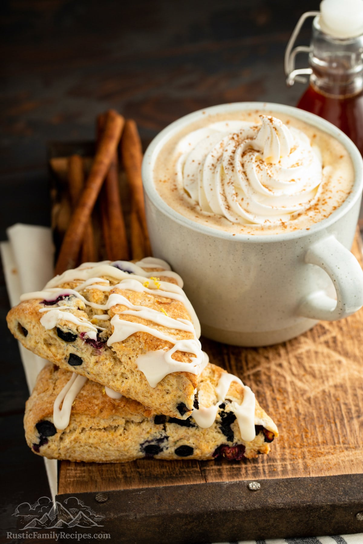 Two glazed blueberry scones stacked next to a Gingerbread Latte.