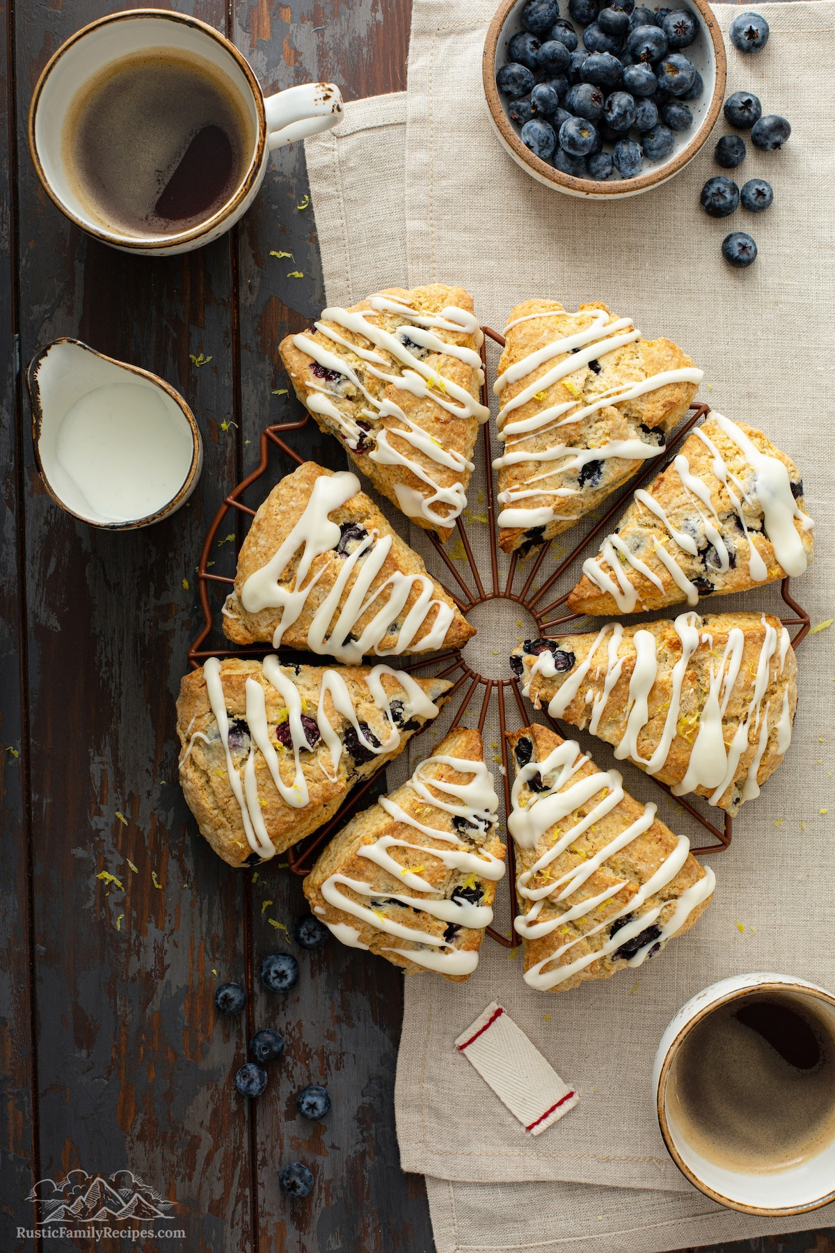 Glazed blueberry scones on a cooling rack next to coffee mugs.