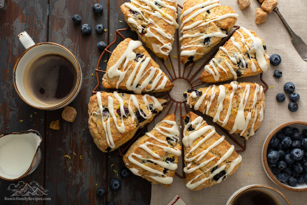 Glazed blueberry scones on a cooling rack next to a cup of coffee.