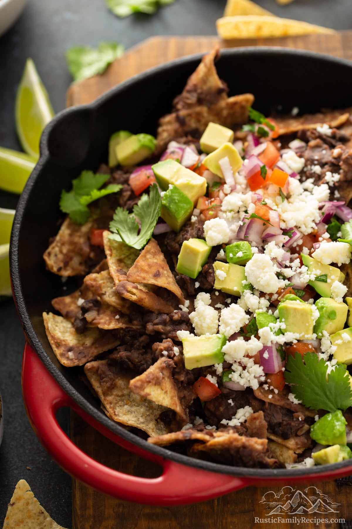 Black bean chilaquiles in a red pan with avocado and cheese