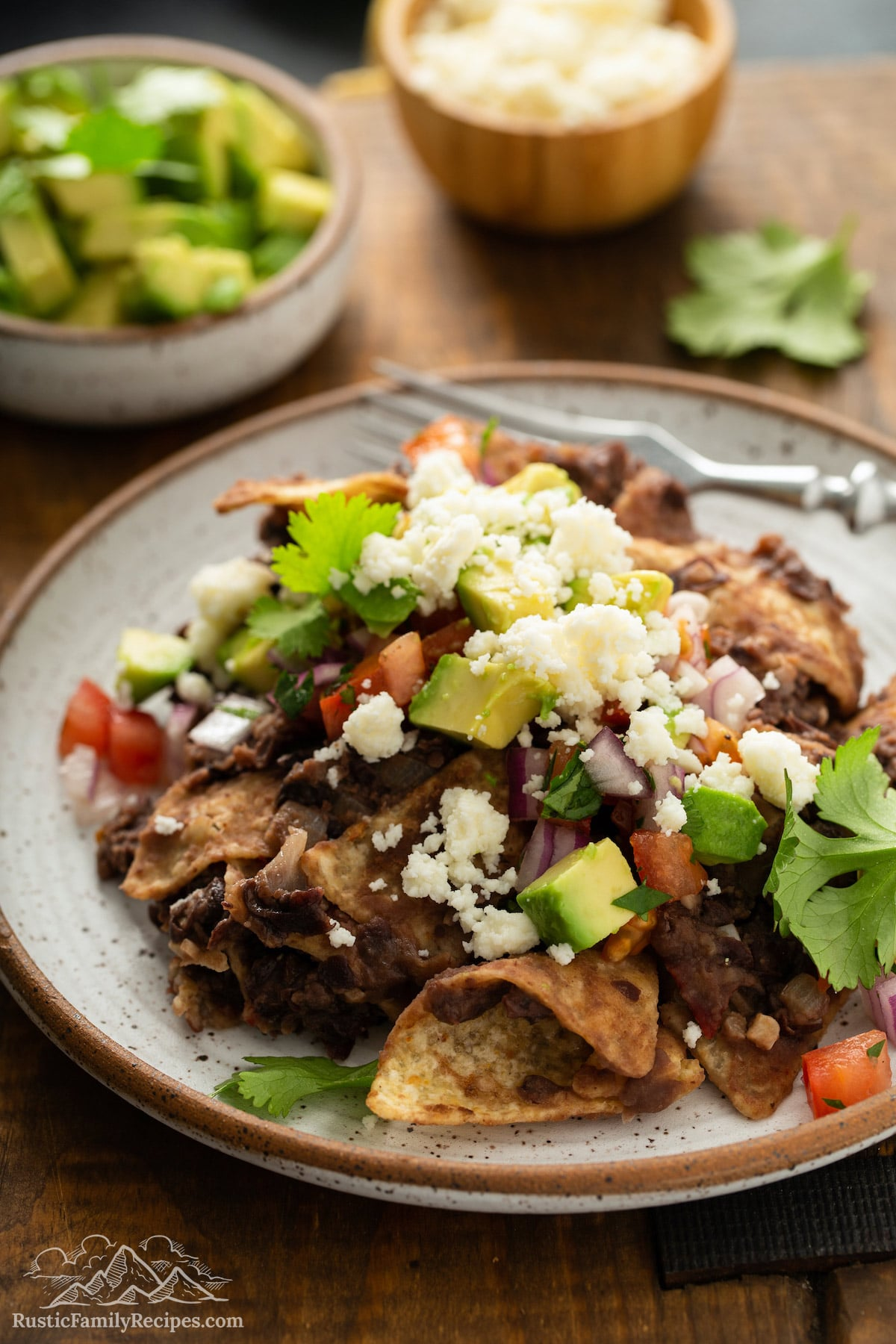 Chilaquiles on a plate topped with salsa, cheese and avocado.