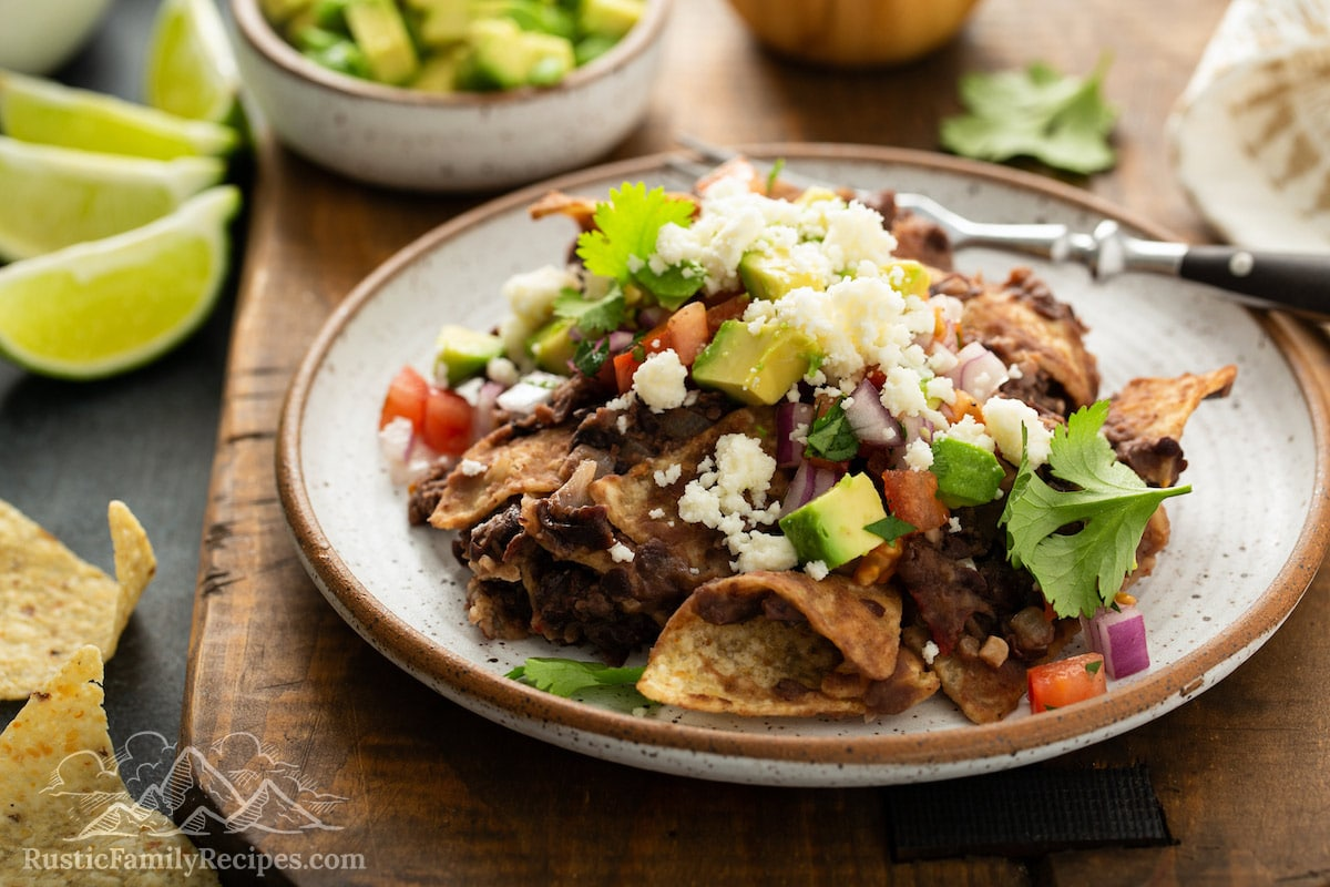 Black bean chilaquiles on a plate with avocado, salsa and cheese