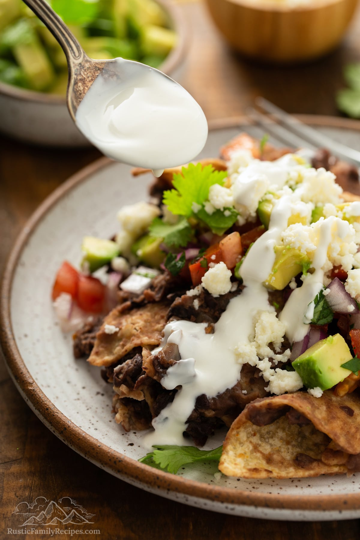 A spoon drizzling sour cream onto chilaquiles.