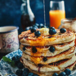 A stack of fluffy pancakes with blueberries, melted butter and syrup