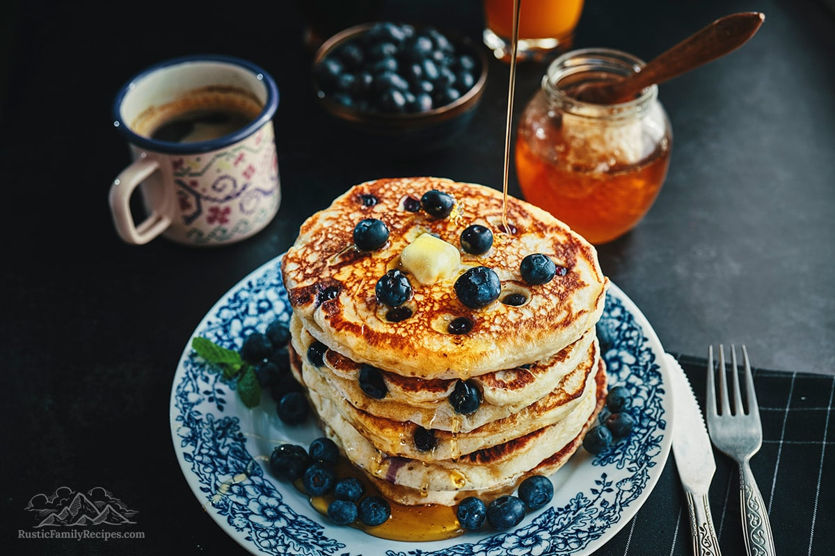 Pouring honey on a stack of multigrain pancakes with butter and blueberries.