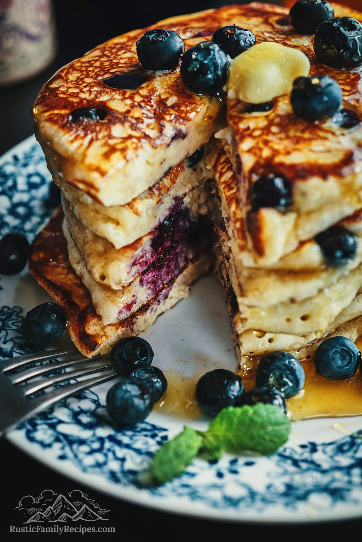 A tall stack of multigrain pancakes with a wedge cut out, topped with blueberries and butter.