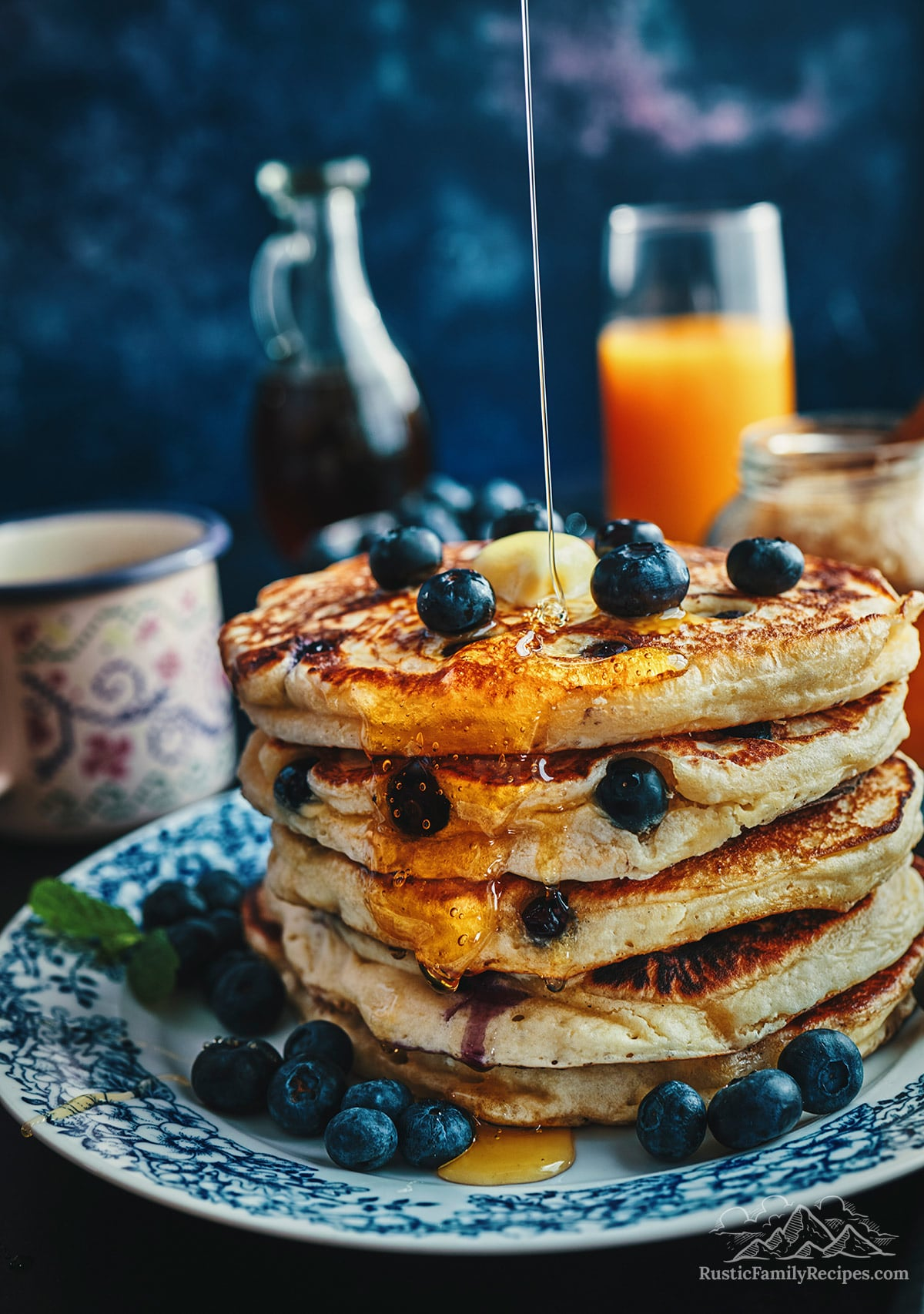 A stack of fluffy blueberry buttermilk pancakes with melted butter, blueberries and syrup.