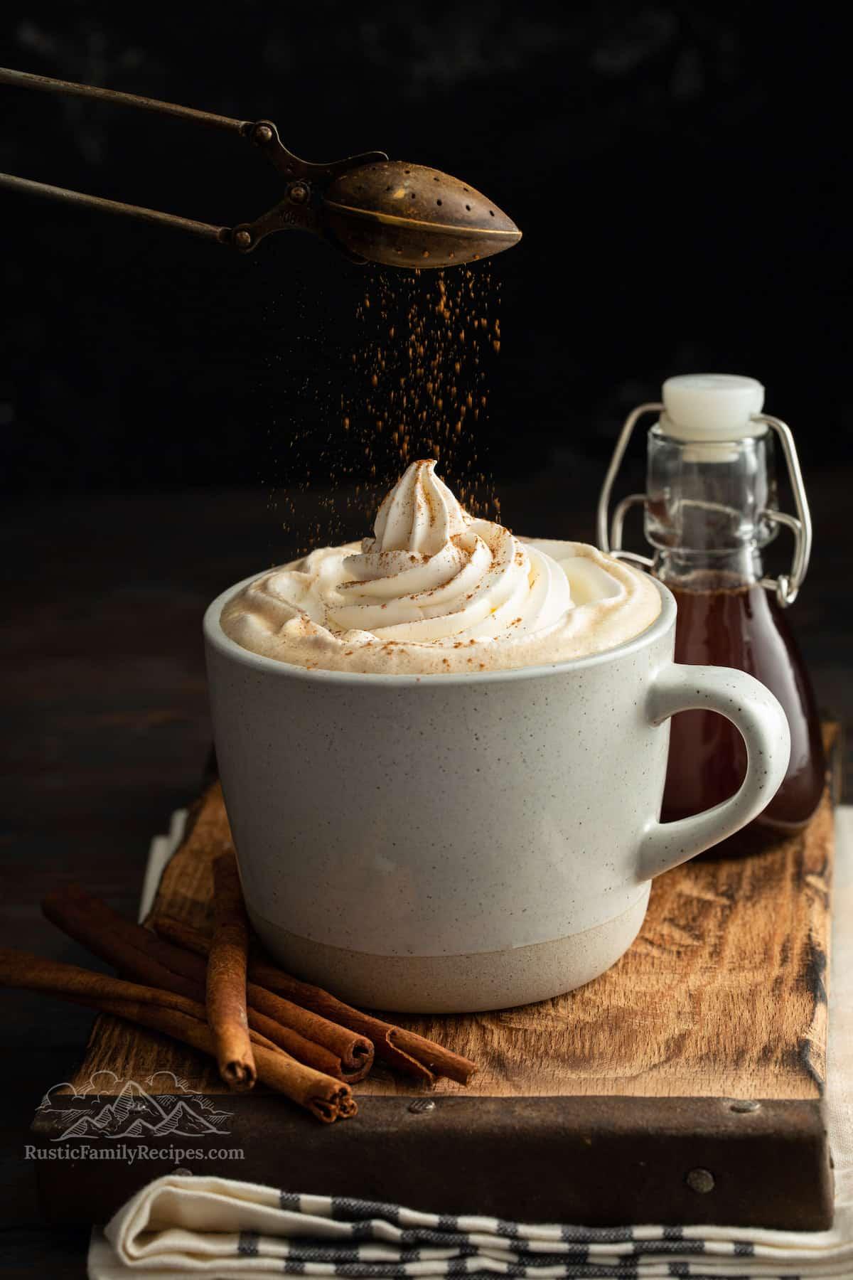 Sprinkling cinnamon on whipped cream in a coffee mug.