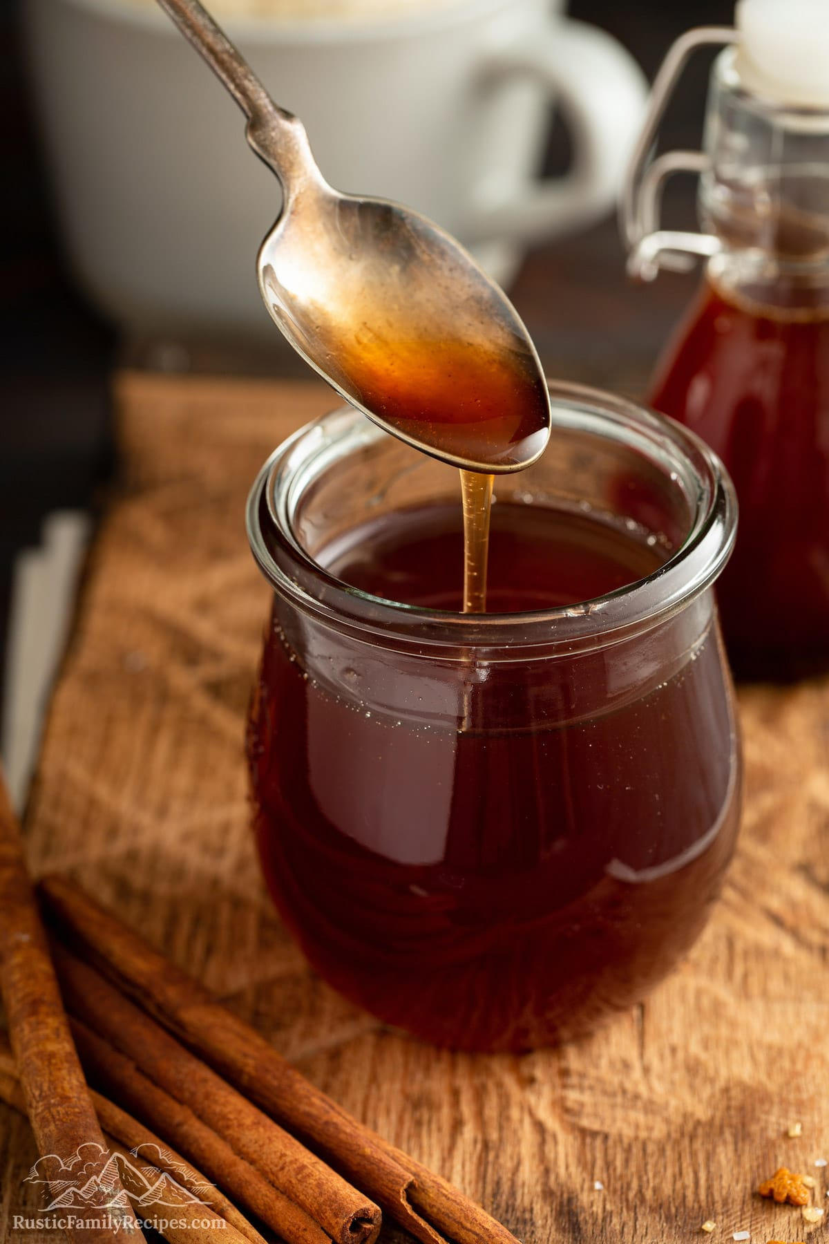 A spoon pouring gingerbread syrup into a jar.