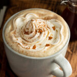 A mug filled with gingerbread latte and topped with whipped cream.