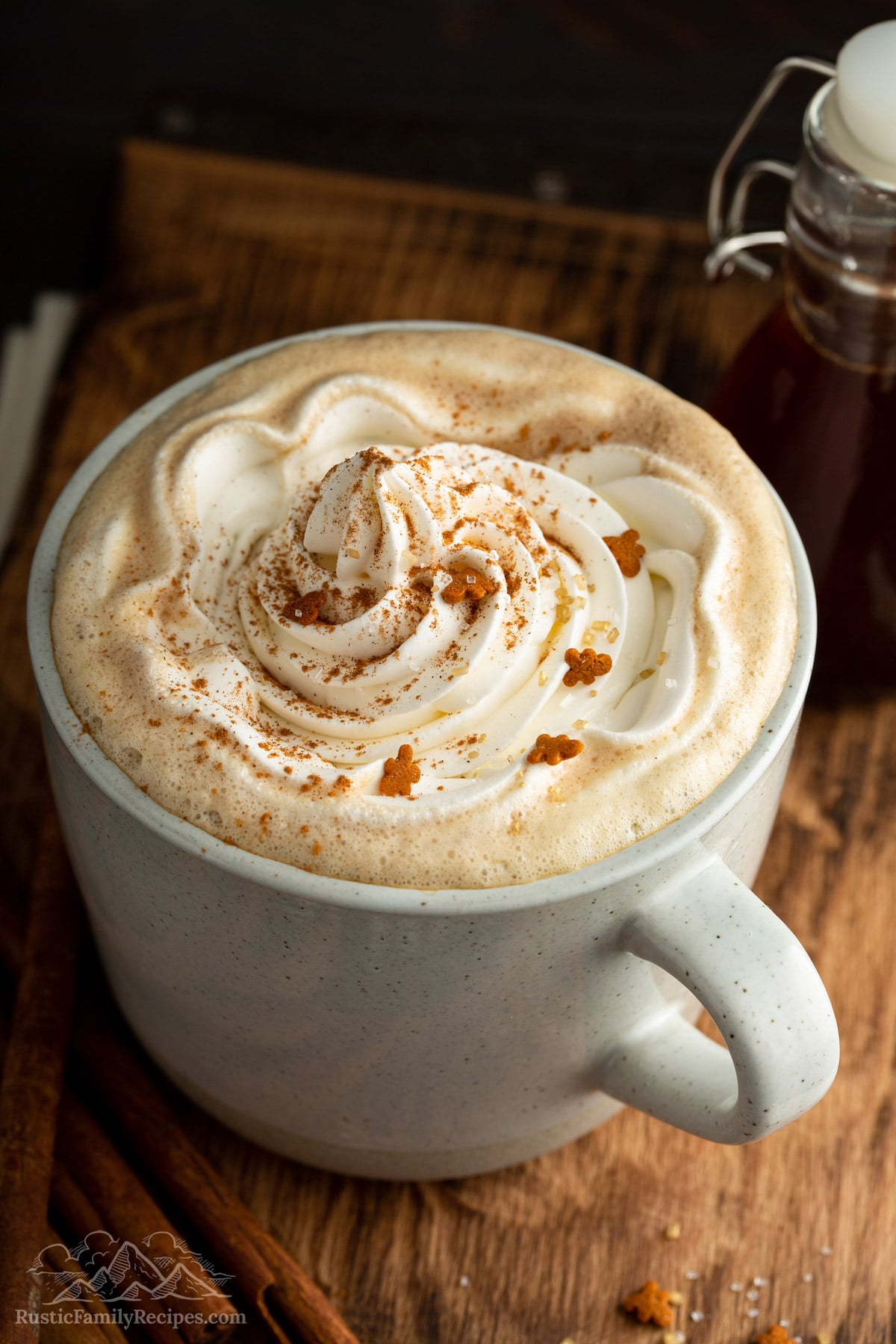 Coffee in a mug tipped with whipped cream and gingerbread sprinkles.