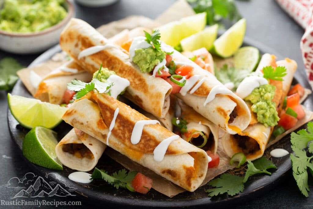 Plate of black bean flautas with lime wedges.