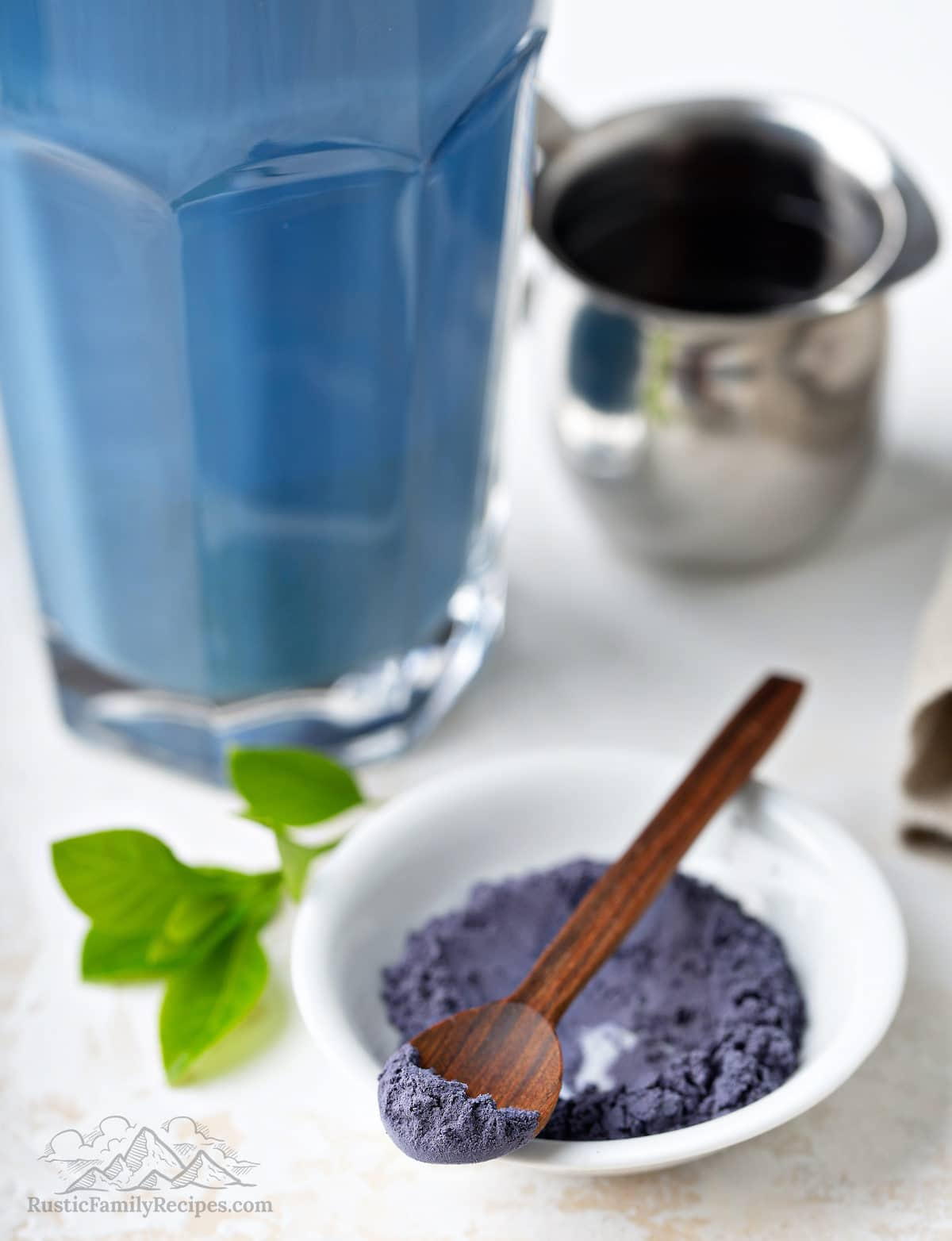A white plate filled with blue matcha powder, a wooden spoon on top with powder.