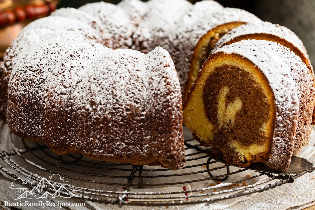 A marble cake with a slice taken out and the swirl visible.