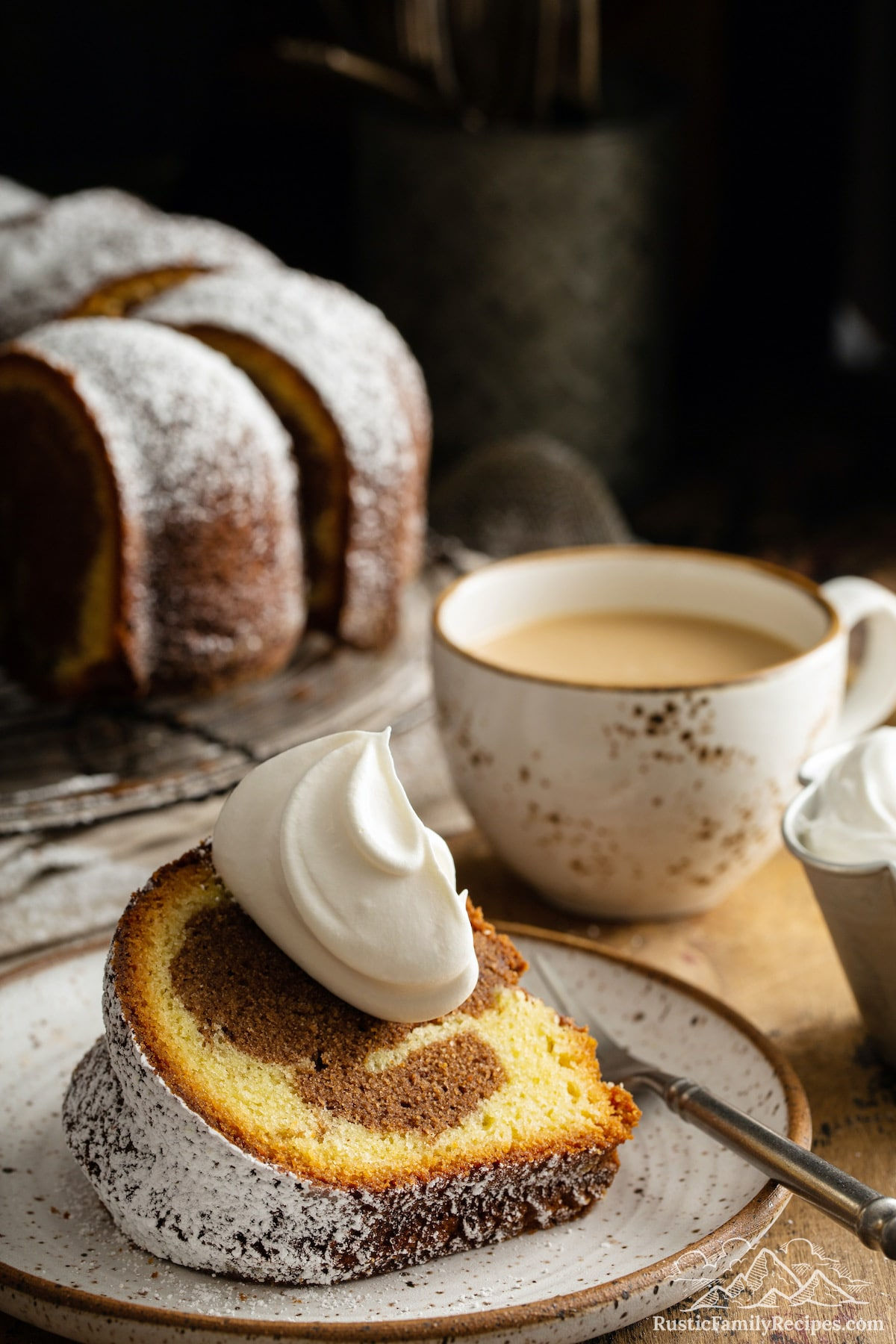 A slice of marble cake topped with a dollop of whipped cream and served with coffee.